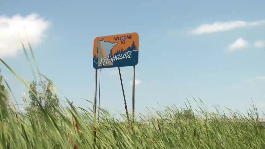 Small blue welcome to Minnesota sign lining a highway leaving North Dakota on side of highway.