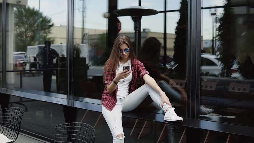 Beautiful woman in branded glasses and casual clothes using her phone near shopwindow   Shutterstock HD Video #32721724
