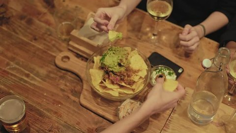 Top view of table at restaurant or bar, where group of friends share bowl of mexican nachos with guacamole and sour cream, while they drink mixed cocktails and alcohol drinks. party snacks