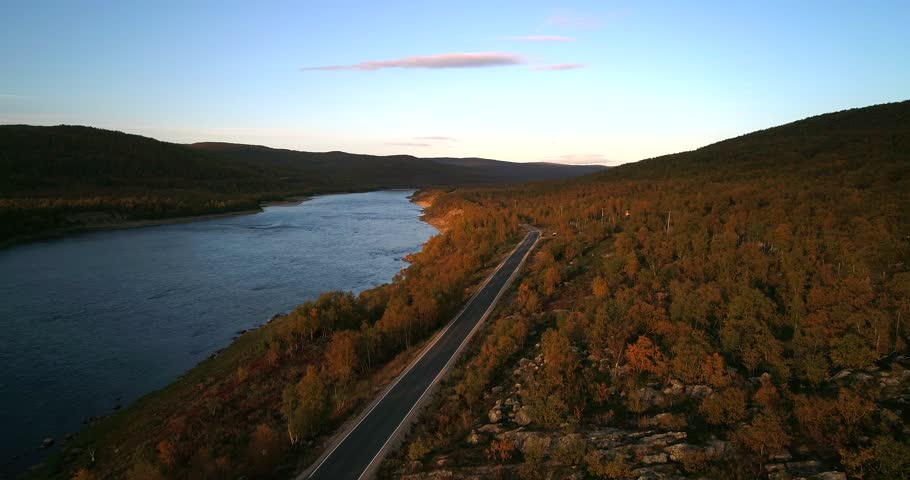 Mountain road, Cinema 4k aerial view over road 970 the tenontie, near tenojoki river, at the border of norway and utsjoki, on a sunny autumn color evening dawn, in utsjoki, Lapland, Finland.mp4