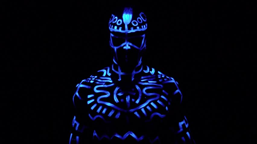 A black man in fluorescent patterns dances in ultraviolet light, slow motion