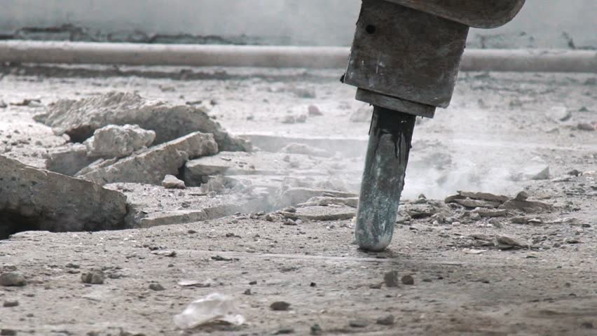 Professional electric tools for breaking the concrete cover. Clay digger in the process of work: close-up. Perforator for the destruction of concrete. Cracks on the floor from the work of a jackhammer