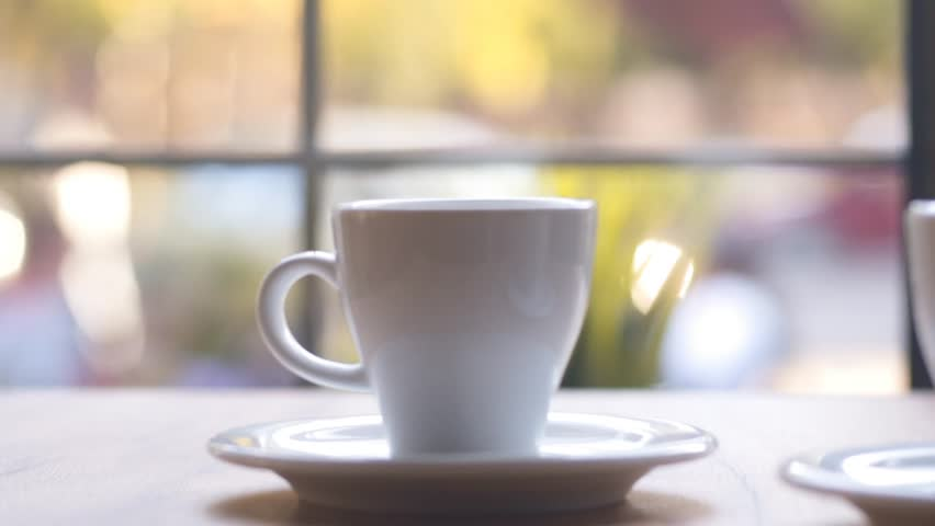 SLOW MOTION: Two cups of espresso coffee on a wooden table indoors. Morning coffee, morning ritual. Coffee for two at home by the window. | Shutterstock HD Video #32784031