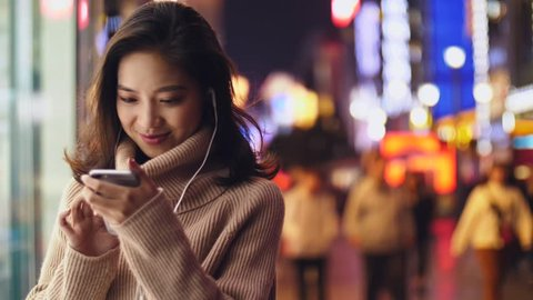 young asian woman using smartphone in the street at night