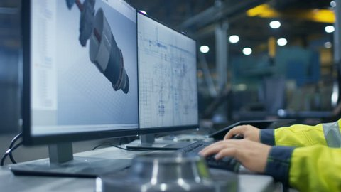 Inside the Heavy Industry Factory Close-up Footage of Industrial Engineer's Hands Working on the Personal Computer with Two Monitors Designing Turbine/ Engine in 3D, Using CAD Program. 4K UHD.