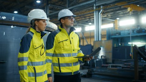 Male and Female Industrial Engineers in Hard Hats and Safety Jackets Discuss New Project while Using Laptop. They Walk Through on a Heavy Industry Manufacturing Factory with Metalwork Components.