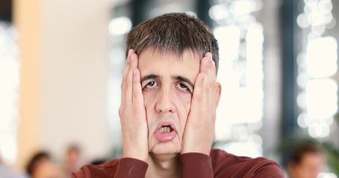The guy clamps his face with his hands making a funny sad face in a public place looks at camera in the interior.
