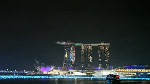 SINGAPORE - DEC 26: Lightshow on top of the Marina Bay Sands hotel at night from a boat on December 26, 2011 in Singapore.
