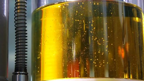 Air small bubbles in yellow engine oil for filter with cellulose, in transparent reservoir, closeup