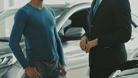 Cropped shot of a happy African man receiving keys to his newly bought car shaking hands with professional car dealer at the dealership salon cars sales business rent service automotive lifestyle