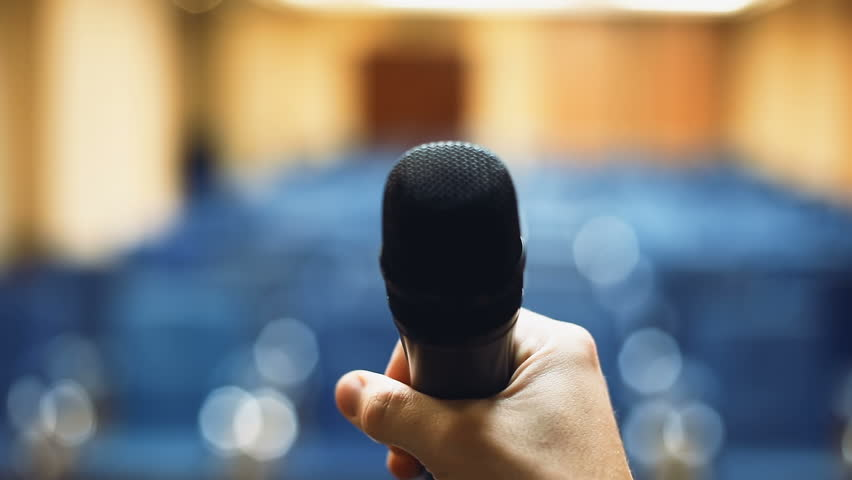 Man holding microphone close-up front view blurred empty meeting room conference hall blue neat rows seats vacant seating place public speech oral speaking speaker business event training seminar | Shutterstock HD Video #32812540