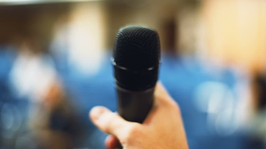 Close up male hand holding microphone blurred conference hall background using mic fear public speech seminar formal meeting lecture speaking skills audience auditourium speechmaking oral presentation | Shutterstock HD Video #32824486