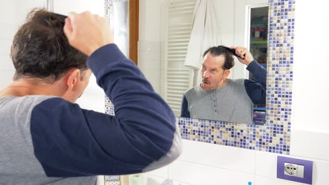 man in front of mirror singing and combing hair funny