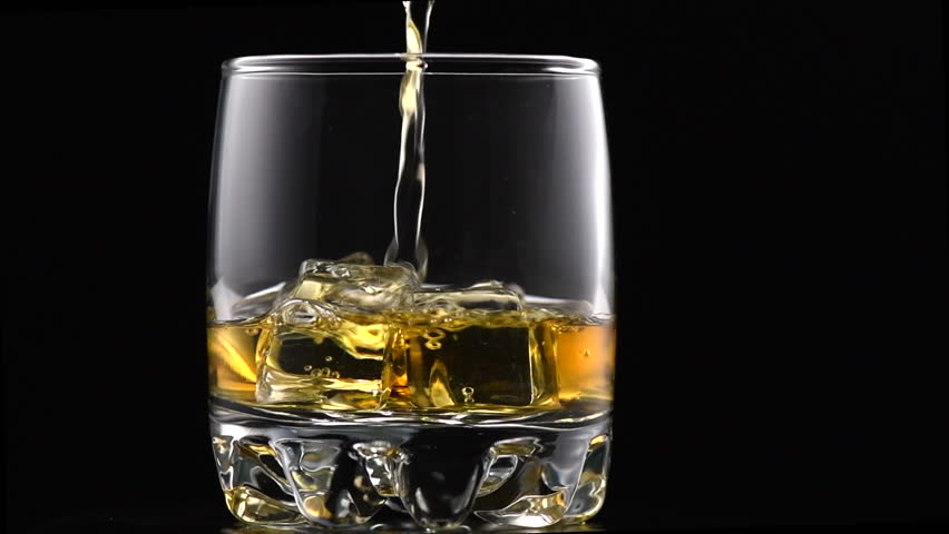 Whiskey with ice. Pouring whisky from the bottle on black background. Glass of rum alcohol close-up. Isolated on black. 4K UHD video