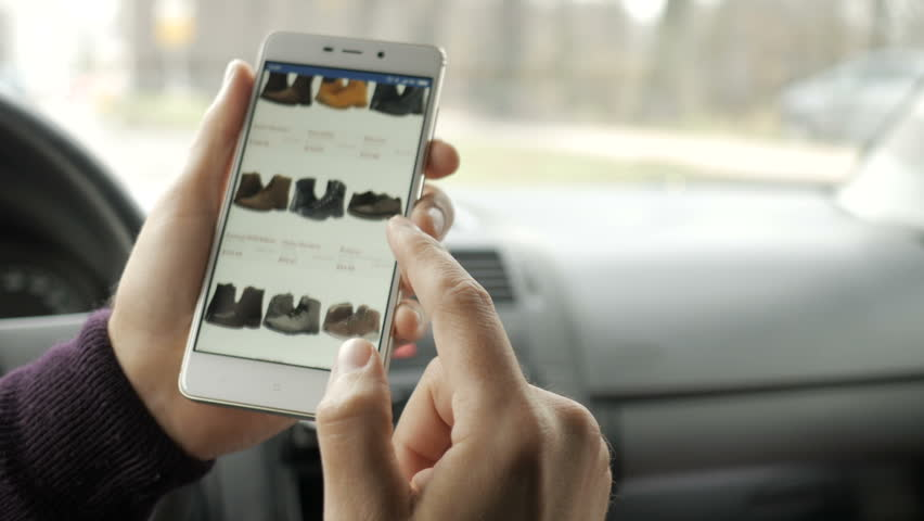 A man looks at the goods in the online shoes store, sitting in the car. Smart phone online shopping.