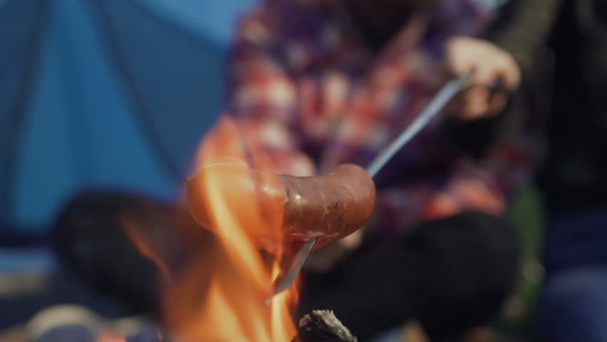 Grilling sausages over a campfire, campers roasting sausages. Tourists are sitting near the flame slow motion
