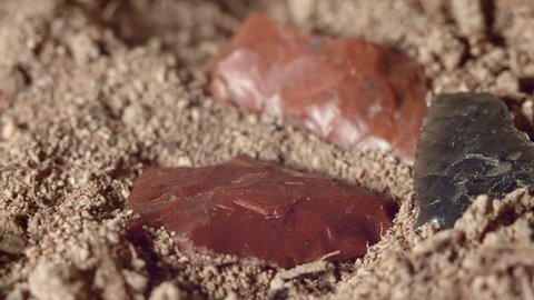 Close up of native American red arrowheads obsidian jasper chert Paiute Indian stone tool in dirt from Oregon great basin desert