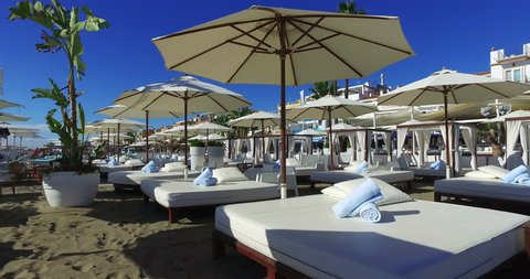 Luxury beach lounge beds with towels &  umbrella at the beach. Sunny weather and a blue sky. Service at your lounge bed enjoying holiday and relaxing. Stabilized movement pan right.