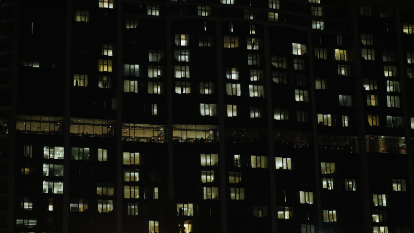 Office building in the dark. The windows are lit, people silhouettes are visible. Tilt shot | Shutterstock HD Video #32907211