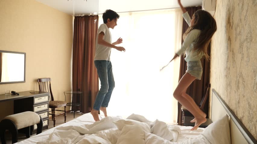Happy laughing brother and sister having a pillow fight. 4k, slow motion
