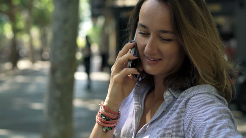 Young, pretty woman talking on cellphone sitting on bench in city    Shutterstock HD Video #32923453