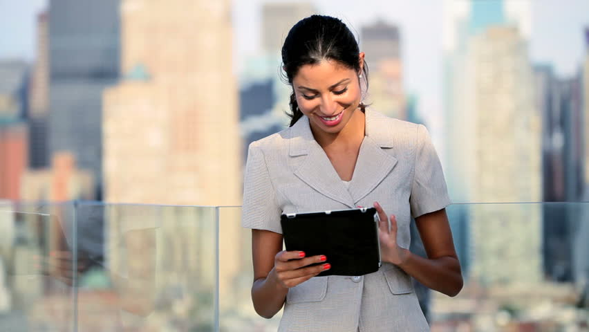 a business woman using a tablet on a rooftop in the big apple