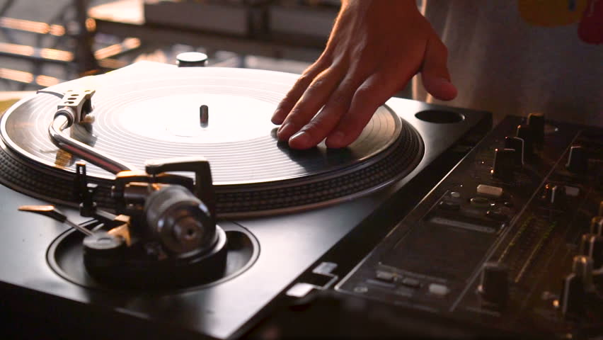 Mix and scratch, hands of a DJ on vinyl and mixer knobs. Slow motion 120 fps. Shooting with gimbal. Sunset.