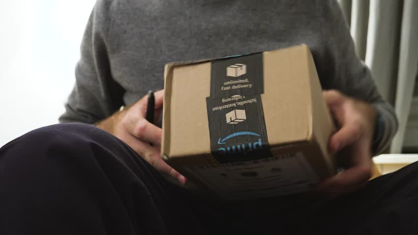 PARIS, FRANCE - CIRCA 2017: Curious male unboxing cardboard box shopping online from Amazon Prime platform - box containing Ricoh Theta V and hahnel Battery for Panasonic GH5 and GH4