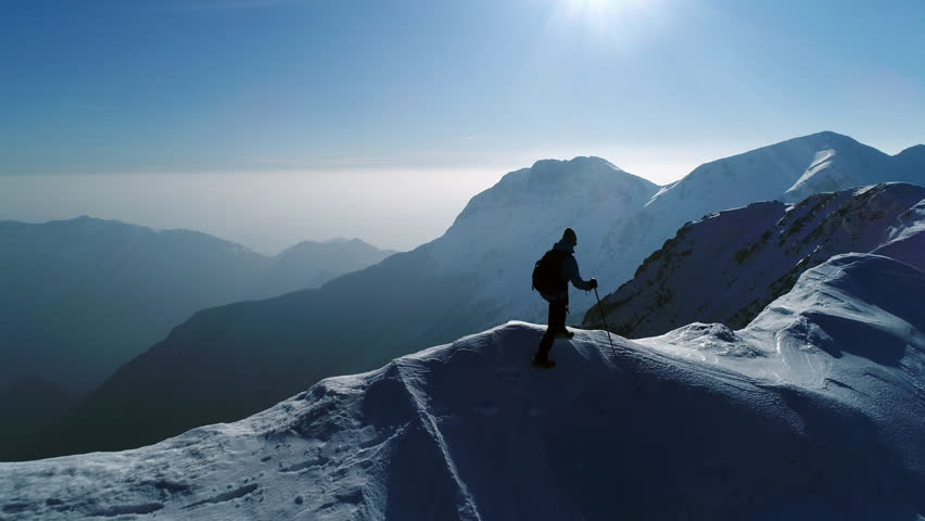 Aerial - Young man hiking on top of snowy mountain at beautiful winter sunset. Male mountaineer with trekking poles and a backpack walking on mountain ridge in Julian Alps #32970271