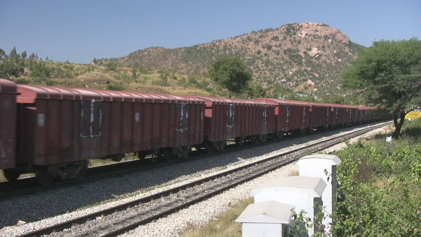 A Freight train is passing by a rural station in India.