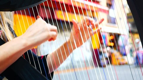 Hands of woman playing a harp. Symphonic orchestra. Harpist close up.