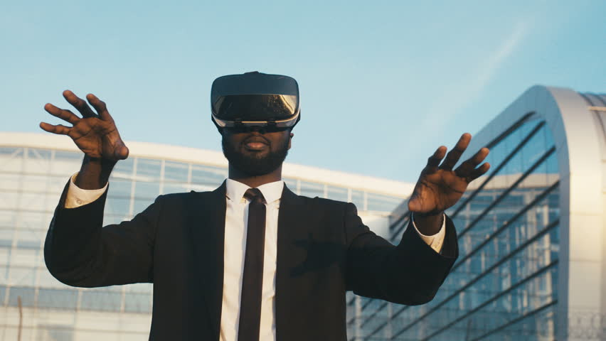 African American young man in suit and tie having VR headset on the big modern glass building background. Businessman in VR glasses in the city. Outdoor. Portrait | Shutterstock HD Video #32979571