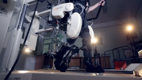 A low view on a man walking inside an exoskeleton.