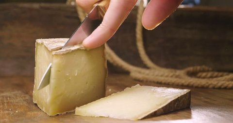 Composition of Italian cheese, on a wooden cutting board. One hand takes the knife and breaks a couple of pieces to savor the quality. Concept of: italy, cheese and tradition.