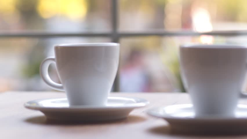SLOW MOTION: Two cups of espresso coffee on a wooden table indoors. Morning coffee, morning ritual. Coffee for two at home by the window. | Shutterstock HD Video #33013651