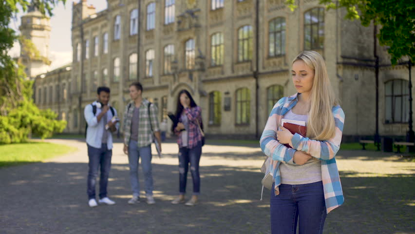 Unfriendly classmates making fun and mocking with sad lonely nerd girl, school | Shutterstock HD Video #33020440