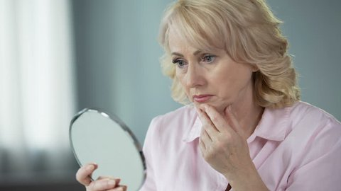 Sad woman looking at face reflection and crying, unhappy with wrinkled skin
