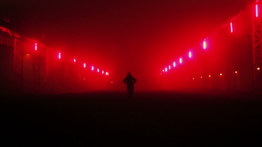 Person jogging in a track illuminated with lanterns color red by night