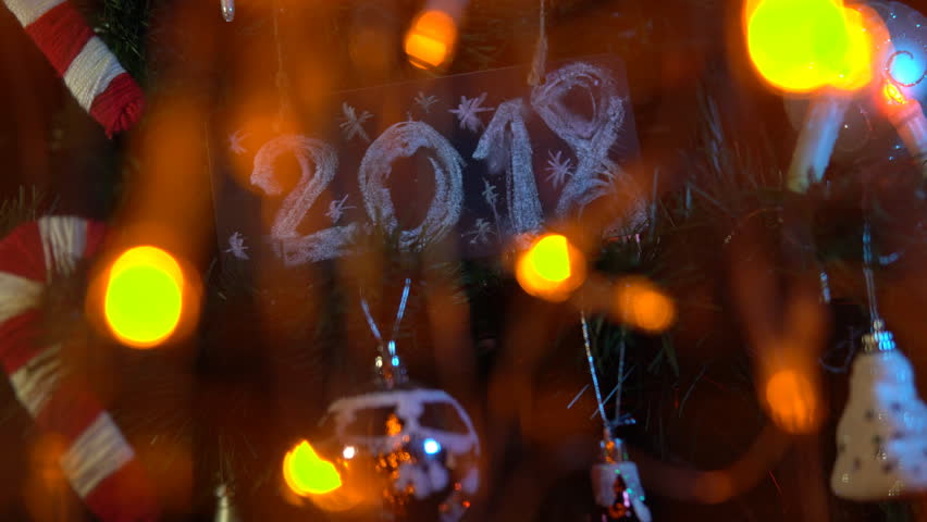 Plate numbered 2018 on a Christmas tree among toys and yellow electric lights, New Year's background. | Shutterstock HD Video #33030637