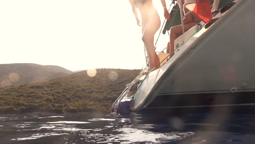 Young woman jumping into sea from boat, super slow motion 240fps