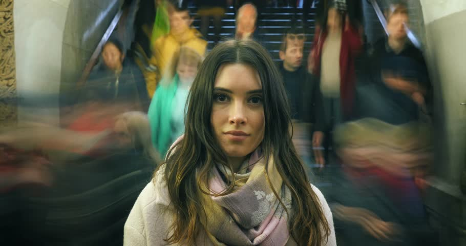 Beautiful young woman looking at camera, closeup. Moving crowd of people blurred in motion in background. 4K UHD timelapse.