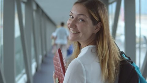 Young handsome woman smiling looking at camera and going to boarding plane at the airport terminal