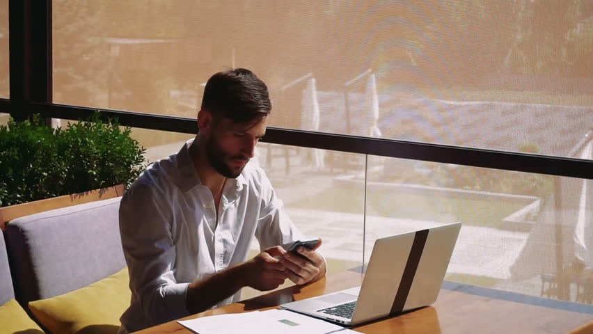 Successful sales manager checking result diagrams, working with laptop and calling marketer indoors. Male person typing number on smartphone looks assured and confident in white shirt. Concept of | Shutterstock HD Video #33075748