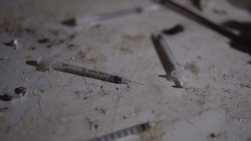 Used Needles For Heroin And Drugs On Dirty Floor Of Abandoned Slum. Homeless And Poverty, Social Issues In Ghetto.
