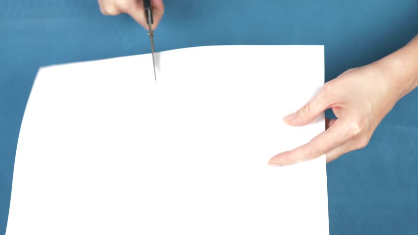 Hands cutting a scissors sheet of paper, closeup on a turquoise background. 4k, slow motion   Shutterstock HD Video #33079015