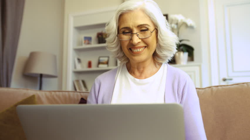 Close up shot of happy old woman in glasses using laptop for video chatting at home in the living room.