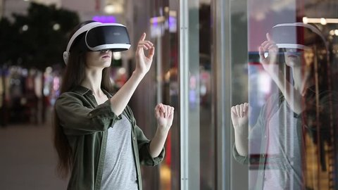 woman uses a virtual reality glasses indoors