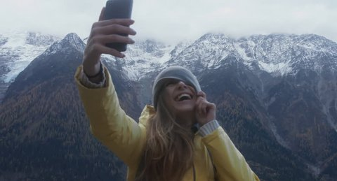 Portrait of beautiful Caucasian female hipster hiker against Mont Blanc massif. 4K UHD RAW 60 FPS SLO MO
