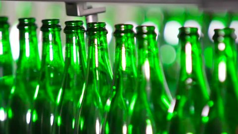 Bottles of green color move along the conveyor at a factory of champagne wines, close-up. Champagne Manufactory.