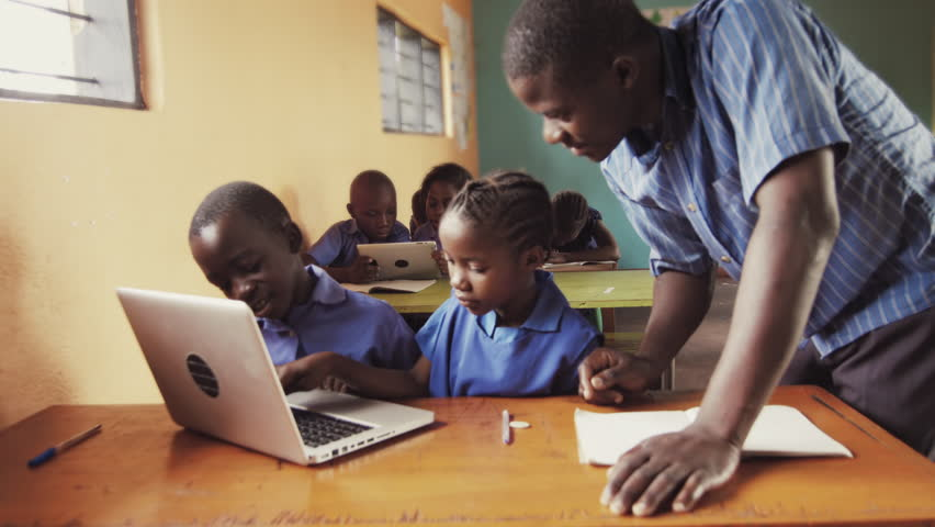 4k of teacher instructing African school students / pupils to use laptop computer in classroom.